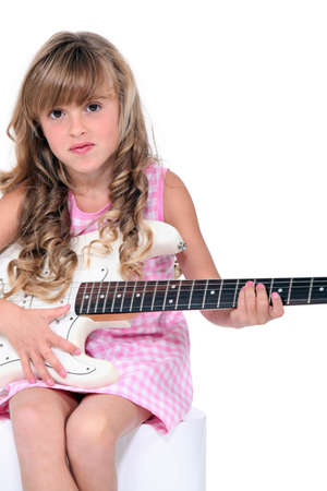 children acting: little girl playing guitar Stock Photo