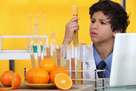 Boy analysing orange juice photo