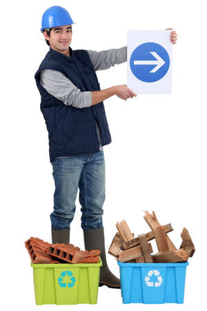 road worker: A construction worker showing the way to recycling. Stock Photo