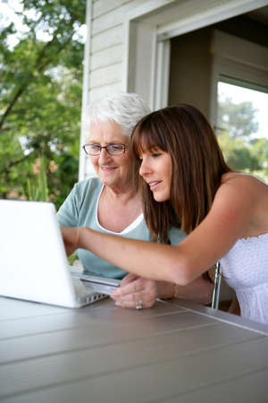 willing: elderly woman and girl with computer Stock Photo