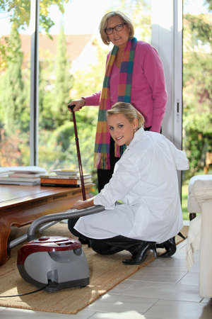 chore: Young woman vacuuming for an elderly lady
