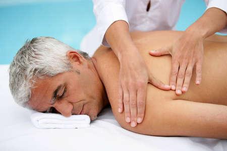 massage homme: L'homme dans le salon de massage Banque d'images