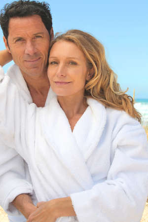 toweling: Man and woman in toweling robes on the beach