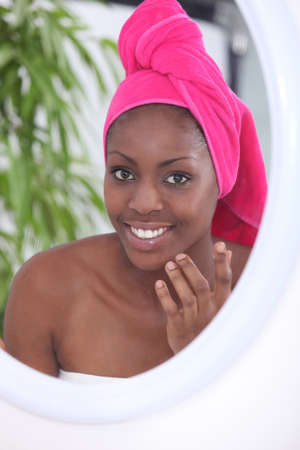 Woman in bathroom with towel on head photo