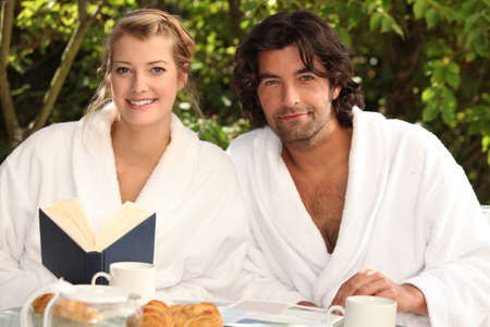 robes: Couple having breakfast in the garden Stock Photo