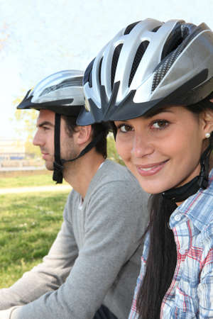 Young couple wearing cycle helmets photo