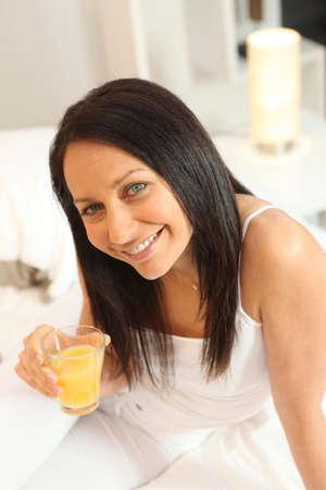 45: Woman drinking a glass of orange juice