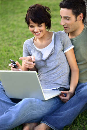 Couple sat in the park with laptop photo