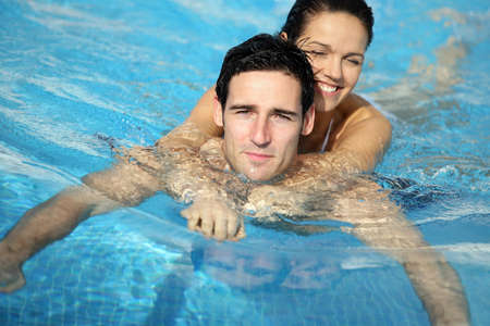 Man and woman embraced in swimming pool photo