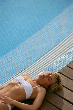 Blond woman resting next to swimming pool photo