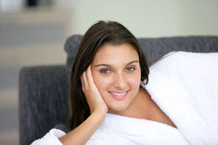 young woman wearing bathrobe lying on the couch photo