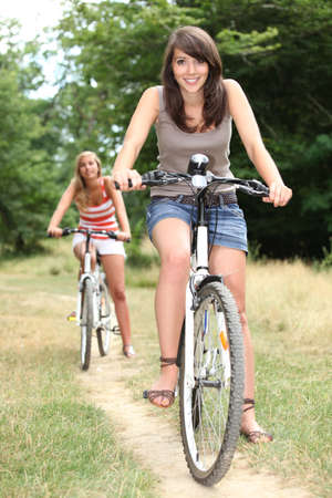 Two teenage girls on bikes in the forest photo