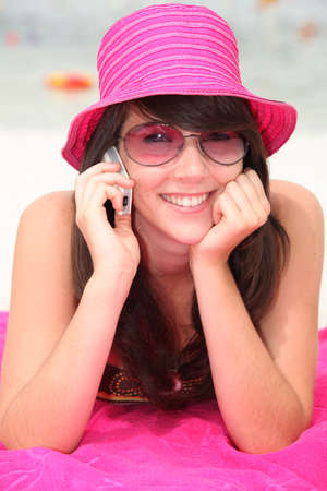 Girl in a shocking pink hat making a call on the beach photo