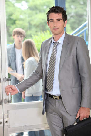Teacher carrying briefcase opening door photo