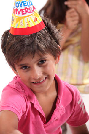 6 7 years: Young boy in a birthday party hat Stock Photo