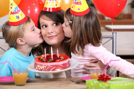 festooned: sisters kissing mom at birthday Stock Photo