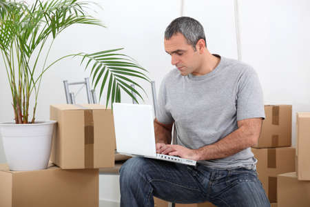 man amid removal boxes working on laptop photo