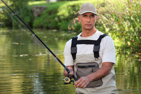 Mature man fishing in a river photo