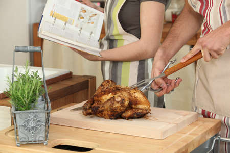 Couple cooking a roast chicken photo