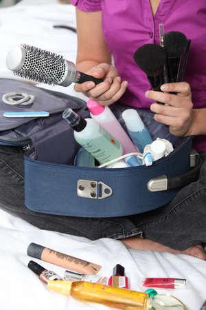 productos de aseo: Mujer preparando su bolsa de maquillaje
