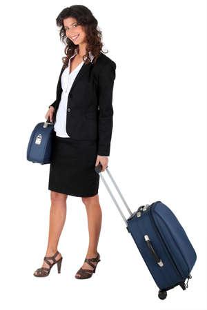 wheeling: Woman wheeling a suitcase