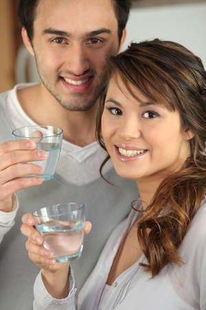 Couple drinking glasses of water photo