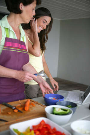 Mother and adult daughter cooking together photo