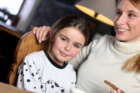 caring for: Woman giving her daughter a snack Stock Photo