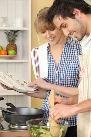 Woman and man smiling cooking using cookbook