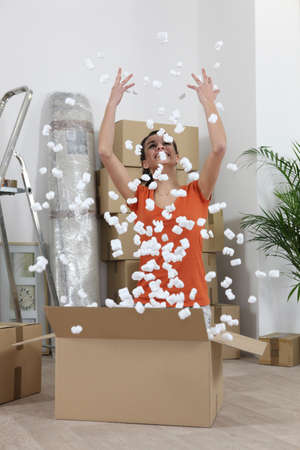Woman excitedly throwing polystyrene peanuts in the air Stock Photo - 12090491