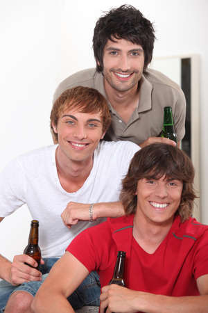 Three lads with bottles of beer photo