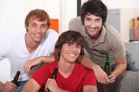 three friends drinking beer at home photo