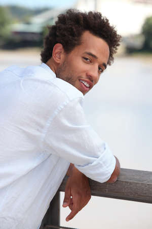 looking forward: Young man leaning on a wooden fence