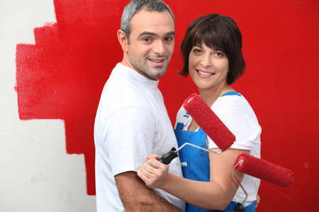 Couple painting a wall red photo