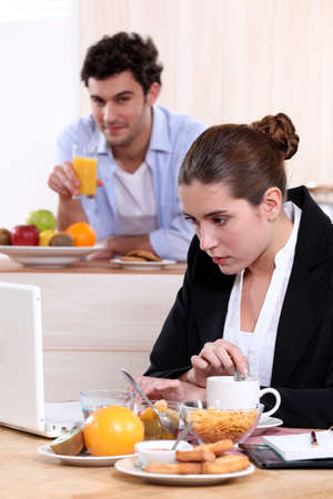 Career woman eating breakfast while working photo