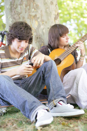 Two teens with guitar sat by tree photo