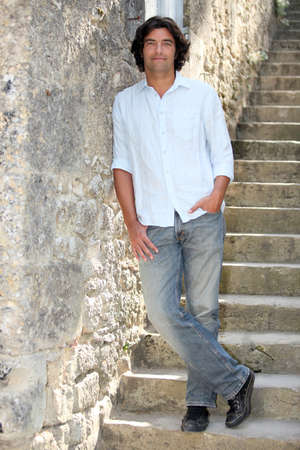 against: Dark haired man leaning against stone wall