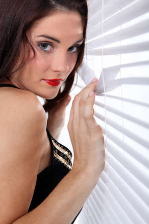 prying: Woman spying through venetian blinds