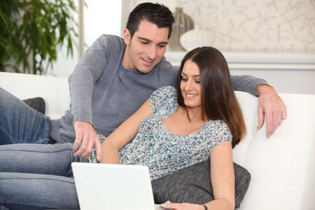 couple couch: Young couple lying on a sofa with a laptop