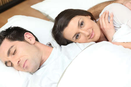 lovers in bed: Young couple lying in bed