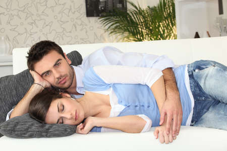 Couple having nap on sofa photo