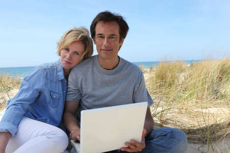Couple on the dunes using laptop computer photo