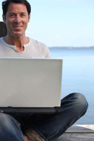 45 49 years: Man using a laptop computer on the waterfront