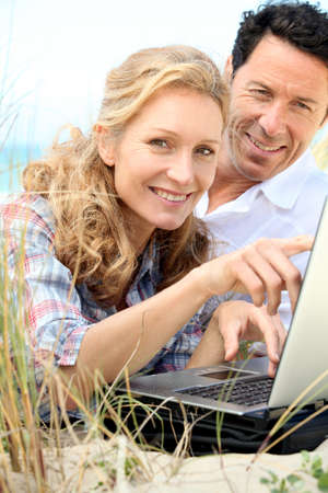 Couple looking at laptop outdoors. photo