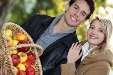 young couple all smiles with basket full of apples photo