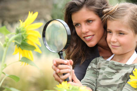 investigative: Young mum and daughter looking at a sunflower through a magnifying glass