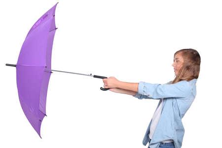 Junge Frau kämpft mit einem violetten Regenschirm an einem windigen Tag