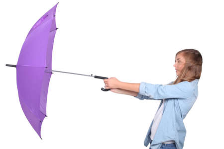 struggling: Young woman struggling with a purple umbrella on a windy day