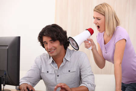 forbidding: a man doing computer and a woman yelling on him with a megaphone