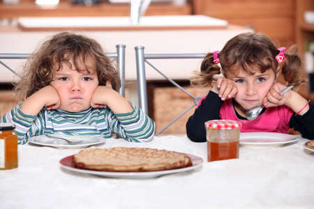 Two grumpy toddlers waiting for their pancakes photo